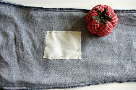 The patch of Fairtrade cotton pinned onto the interfacing which covers the hole