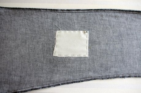 The Fairtrade cotton patch hand-stiched over the interfacing and covering the hole